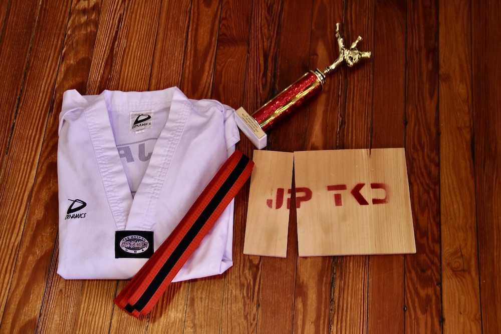 The author's Taekwondo uniform, red belt with a black stripe, trophy, and broken wooden board. Photo taken by the author.