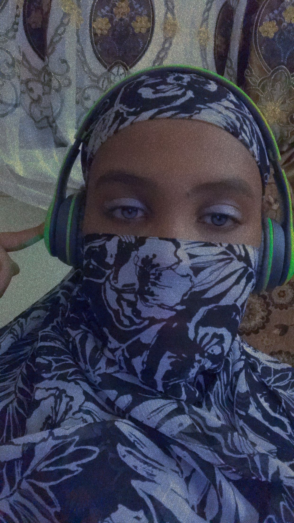 A photo of the author in their hijab, also wearing over-ear headphones. Photo taken by the author.