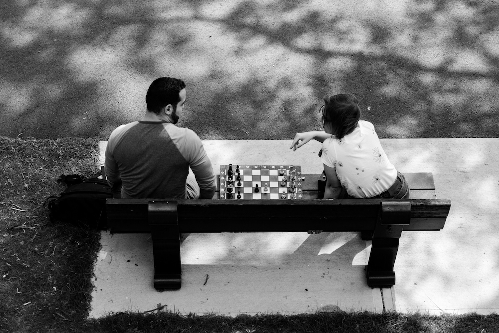 Two people play chess on a bench. Photo taken by the author.