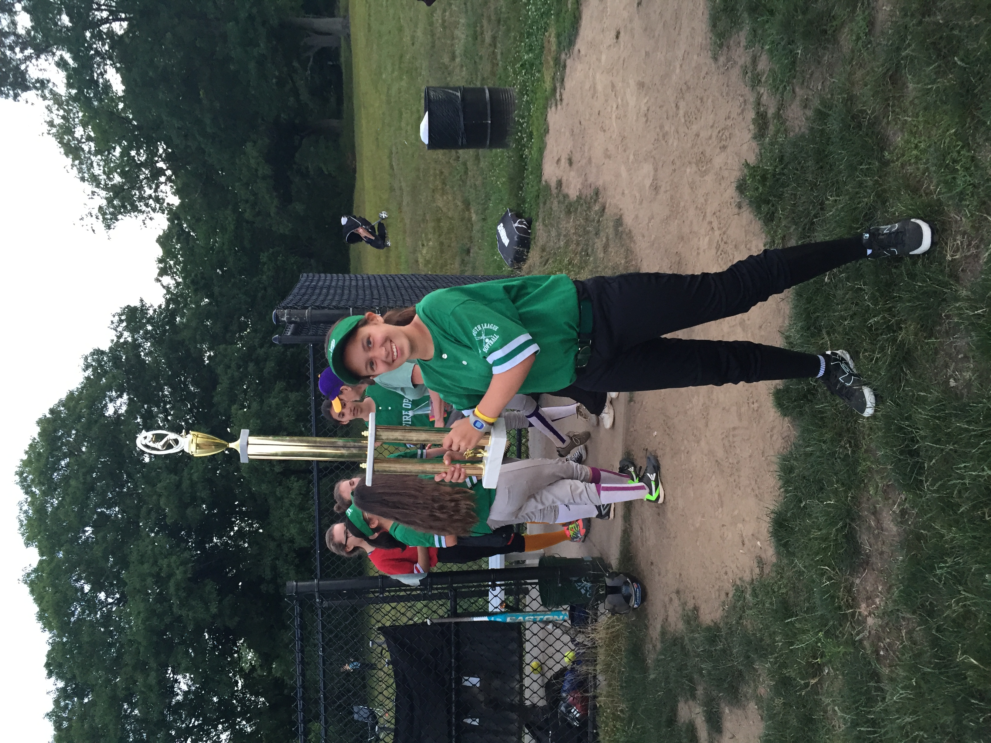 The author holds a large softball trophy. Photo courtesy of the author.