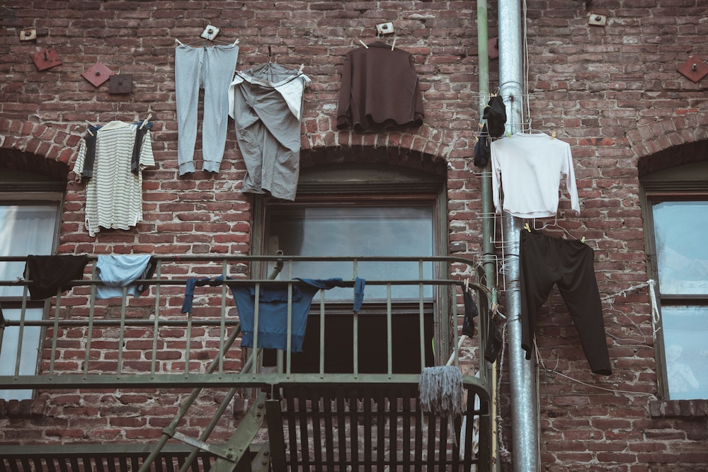 Various items of clothing hanging from a brick building. Photo courtesy of Ernest Karchmit on Unsplash.