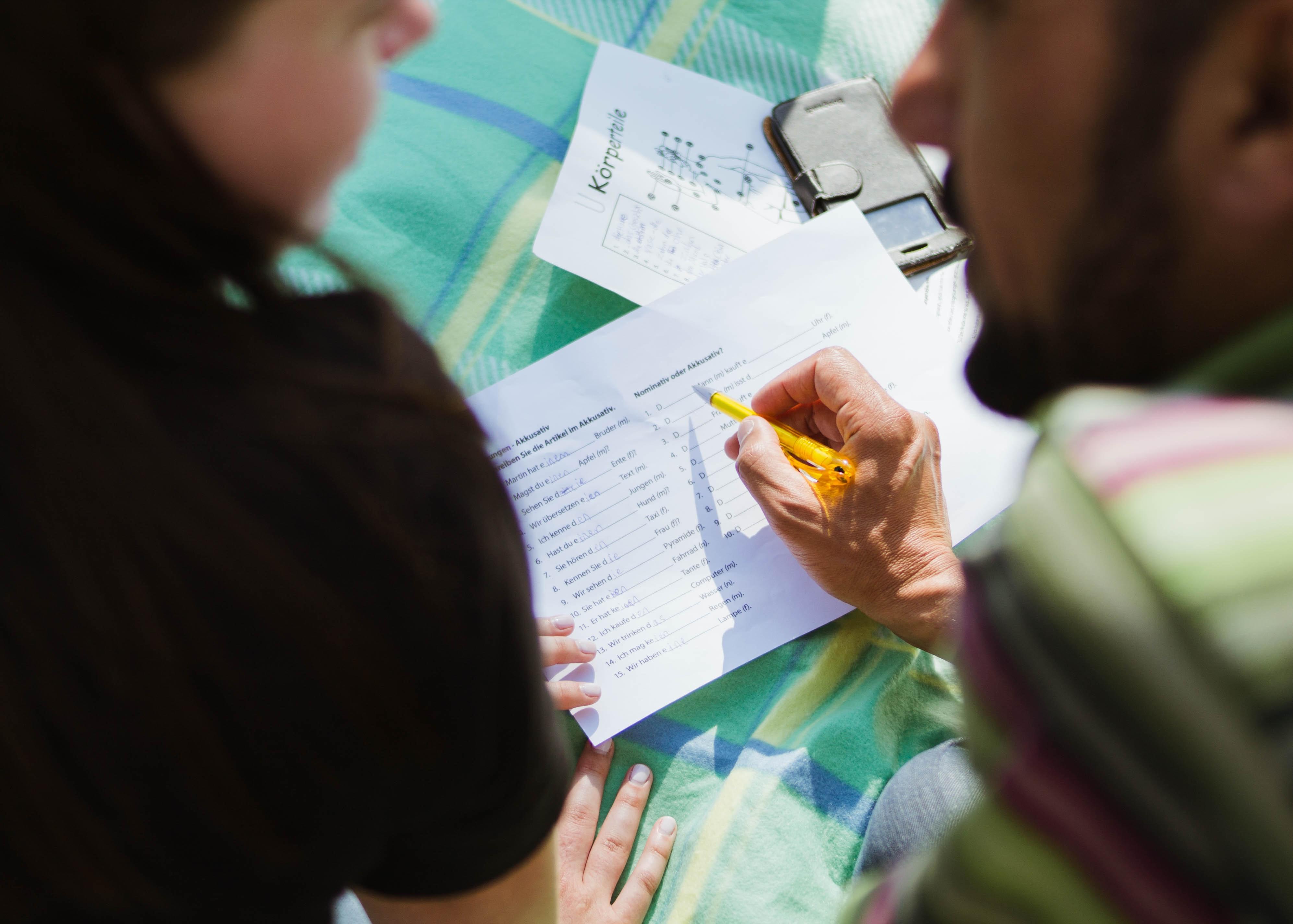 A teacher working with a student. Photo courtesy of Annika Gordon on Unsplash.