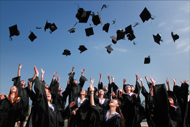 Students throw graduation caps in the air. Photo courtesy of Pixabay on Pexels.