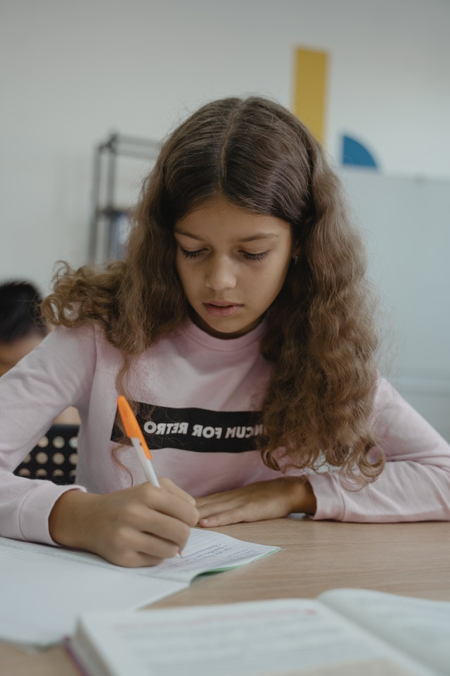 Student writing notes in an answer booklet. Photo courtesy of Tima Miroshnichenko on Pexels.