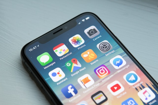 An iPhone displaying apps on the home screen. Photo courtesy of William Hook on Unsplash.