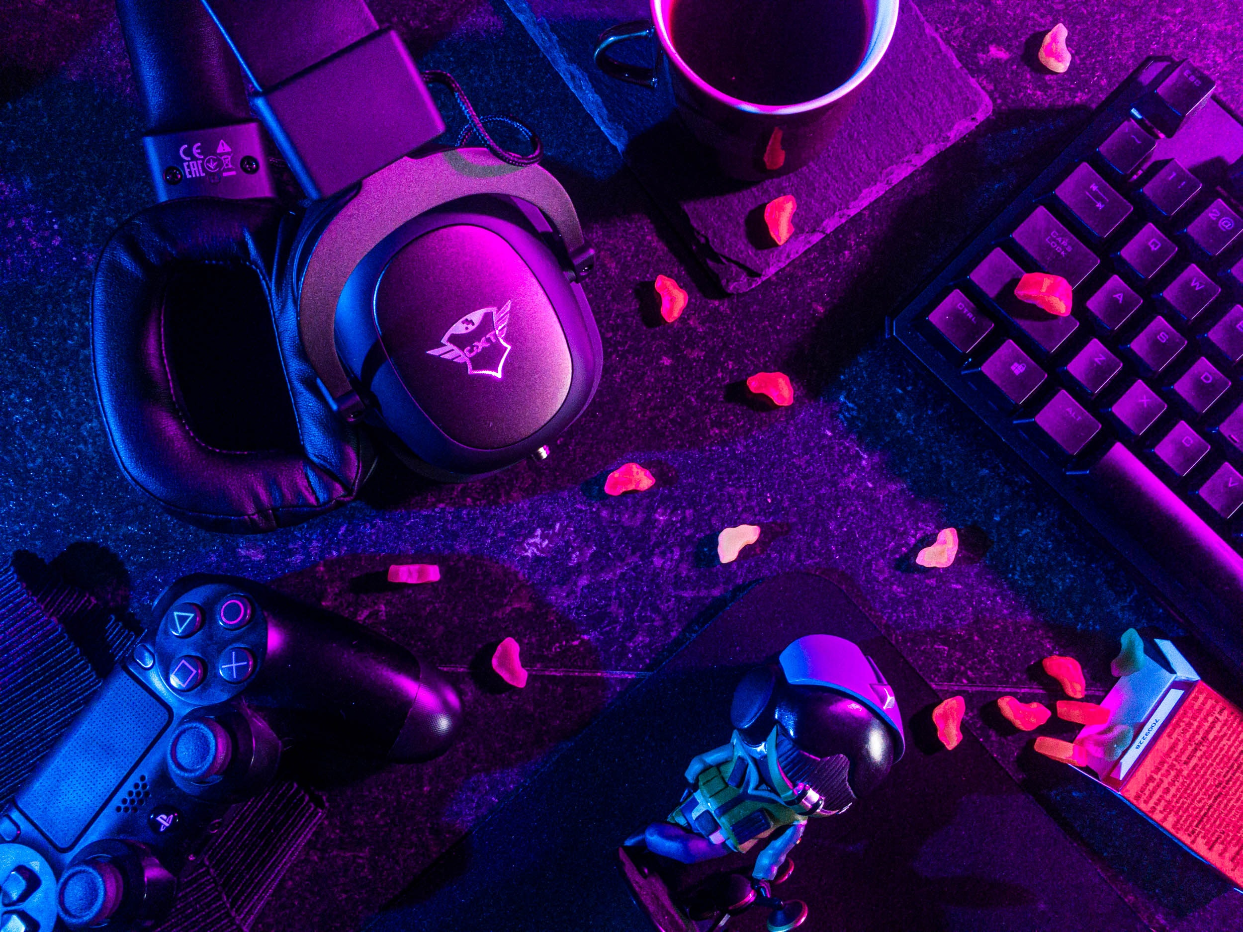 Headphones and video game controllers under purple and pink lighting. Photo courtesy of Lucie Liz on Pexels.