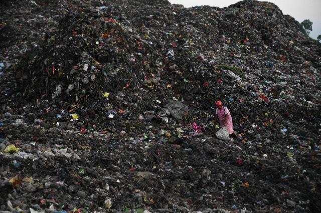 Photo of a person collecting trash in a landfill. Photo courtesy of Mumtahinna Tanni on Pexels.