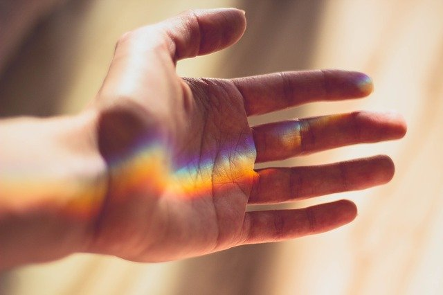 Rainbow light touching the palm of a hand. Photo courtesy of cm_dasilva on Pexels.
