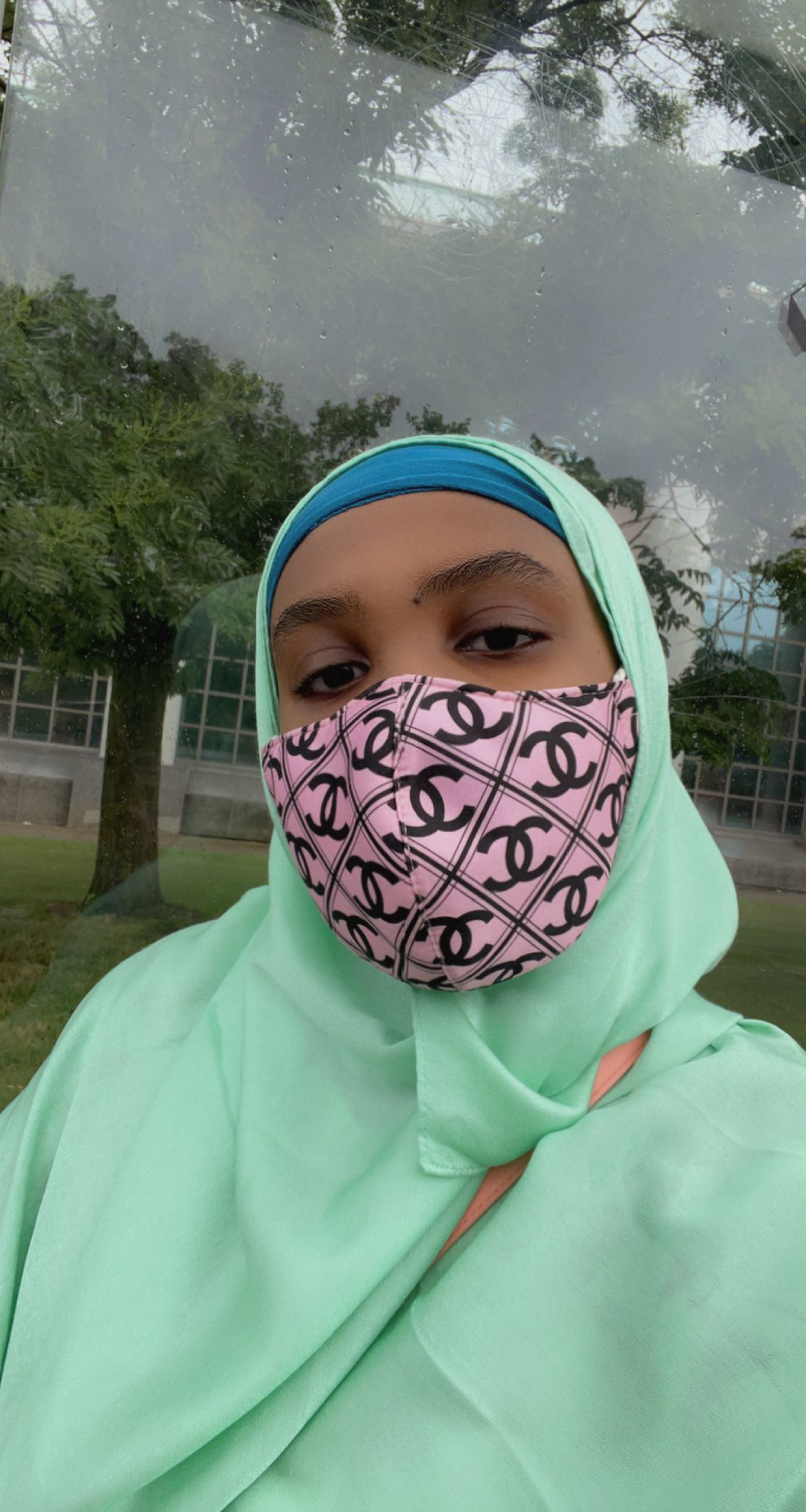 Selfie of the author in a lime green scarf, blue headband, and pink face mask. Photo taken by the author.