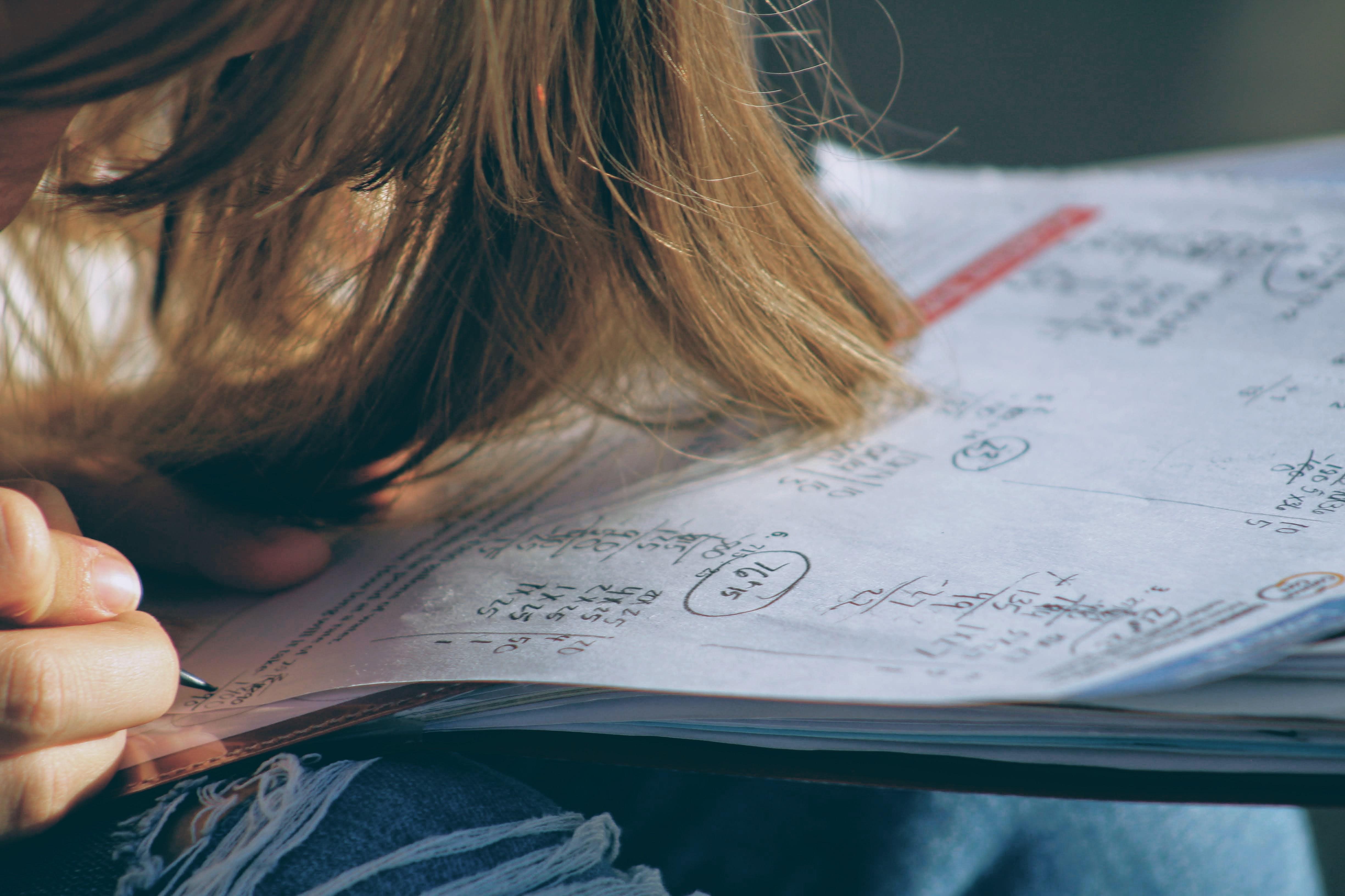 A student's hair over math homewor. Photo courtesy of Joshua Hoehne on Unsplash.