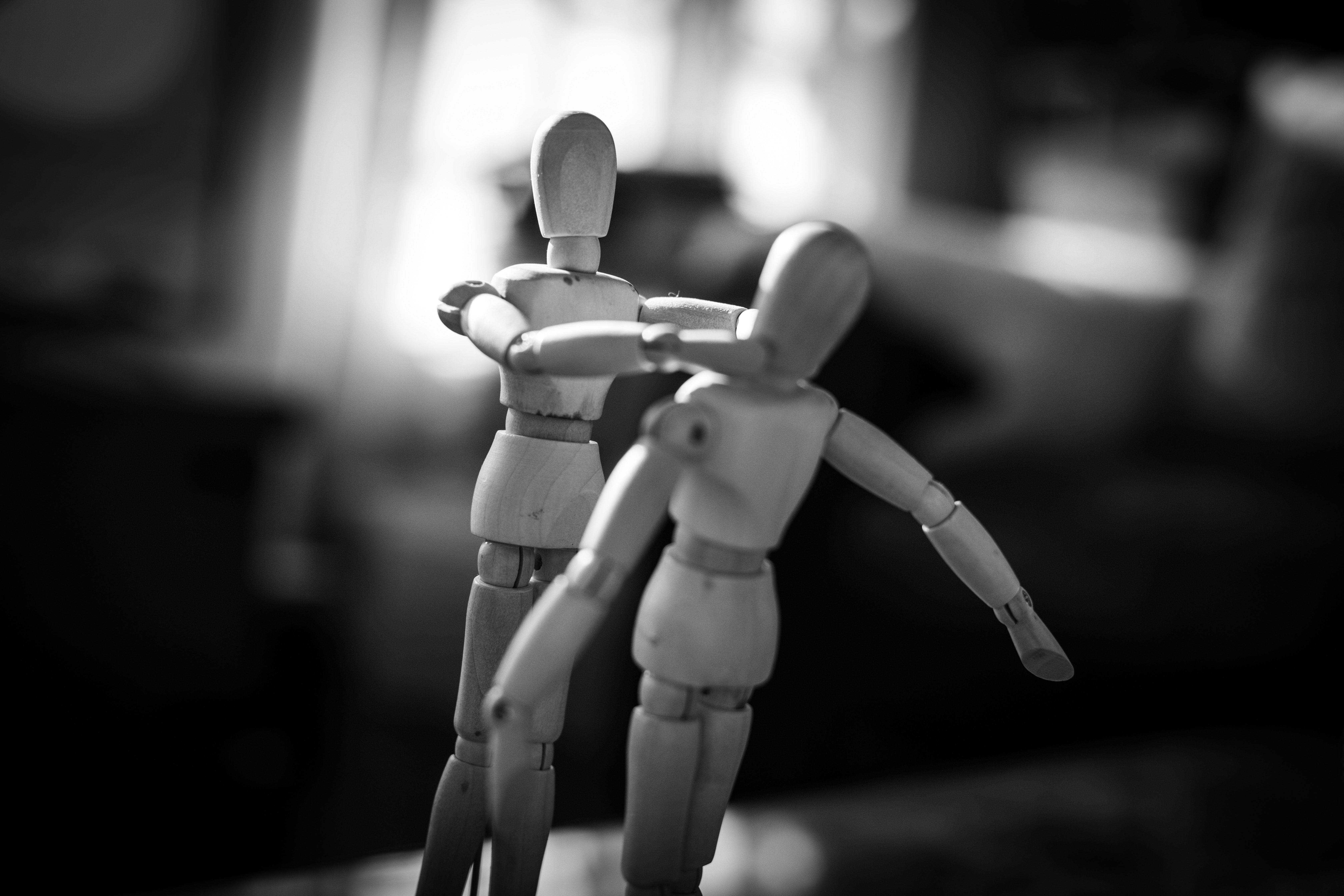 Two wooden mannequins standing in front of each other, the one on the left has its hands on the other's face. Photo courtesy of Charl Folscher on Unsplash.