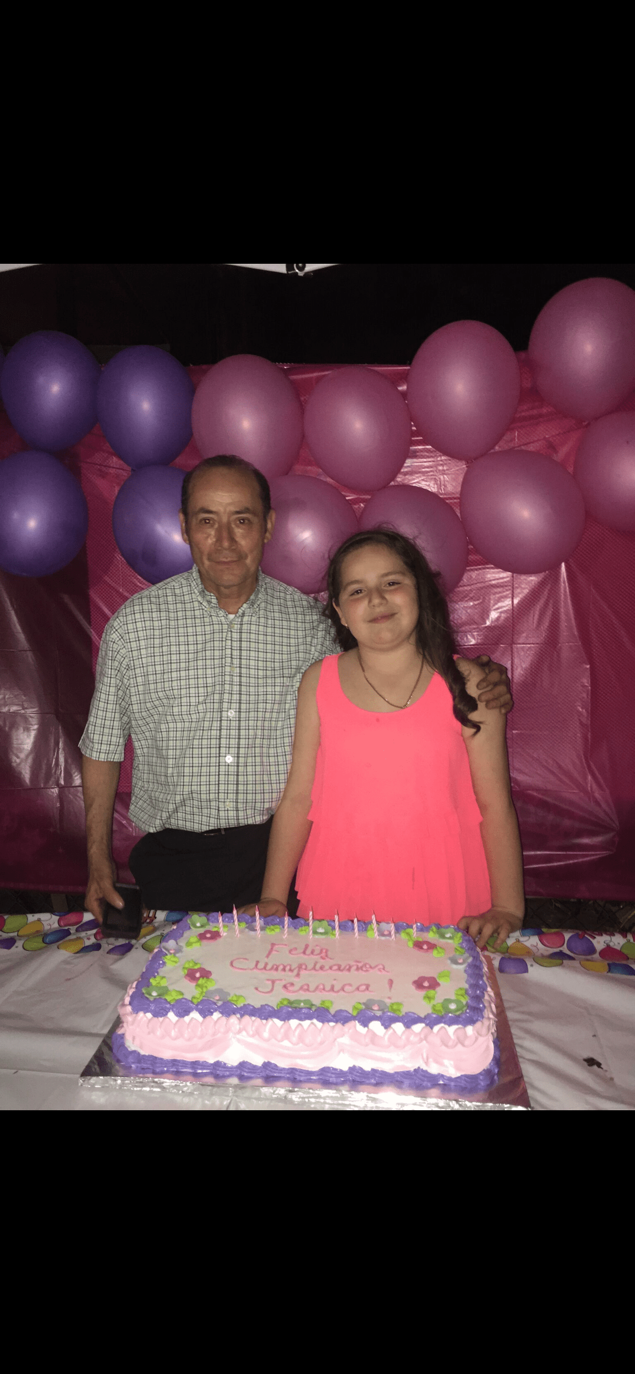 Photo of the author and her grandfather standing in front of her birthday cake. Photo courtesy of the author.