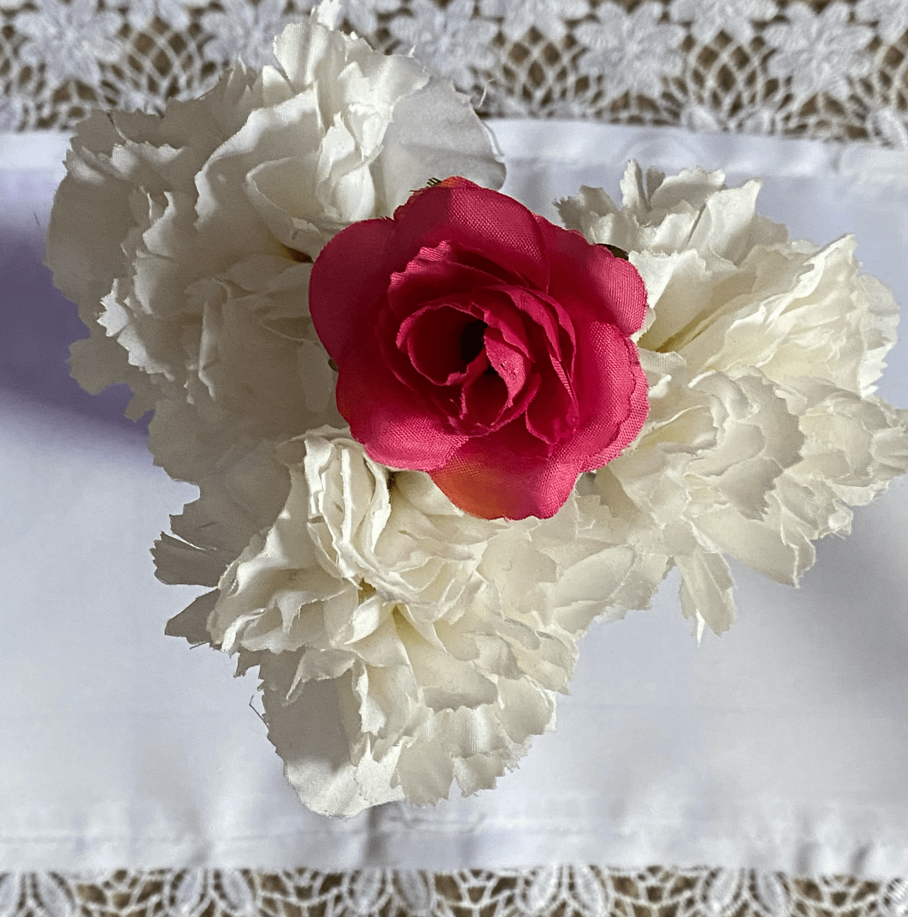 Photo of an artificial rose surrounded by white flowers on a table. Photo courtesy of the author.