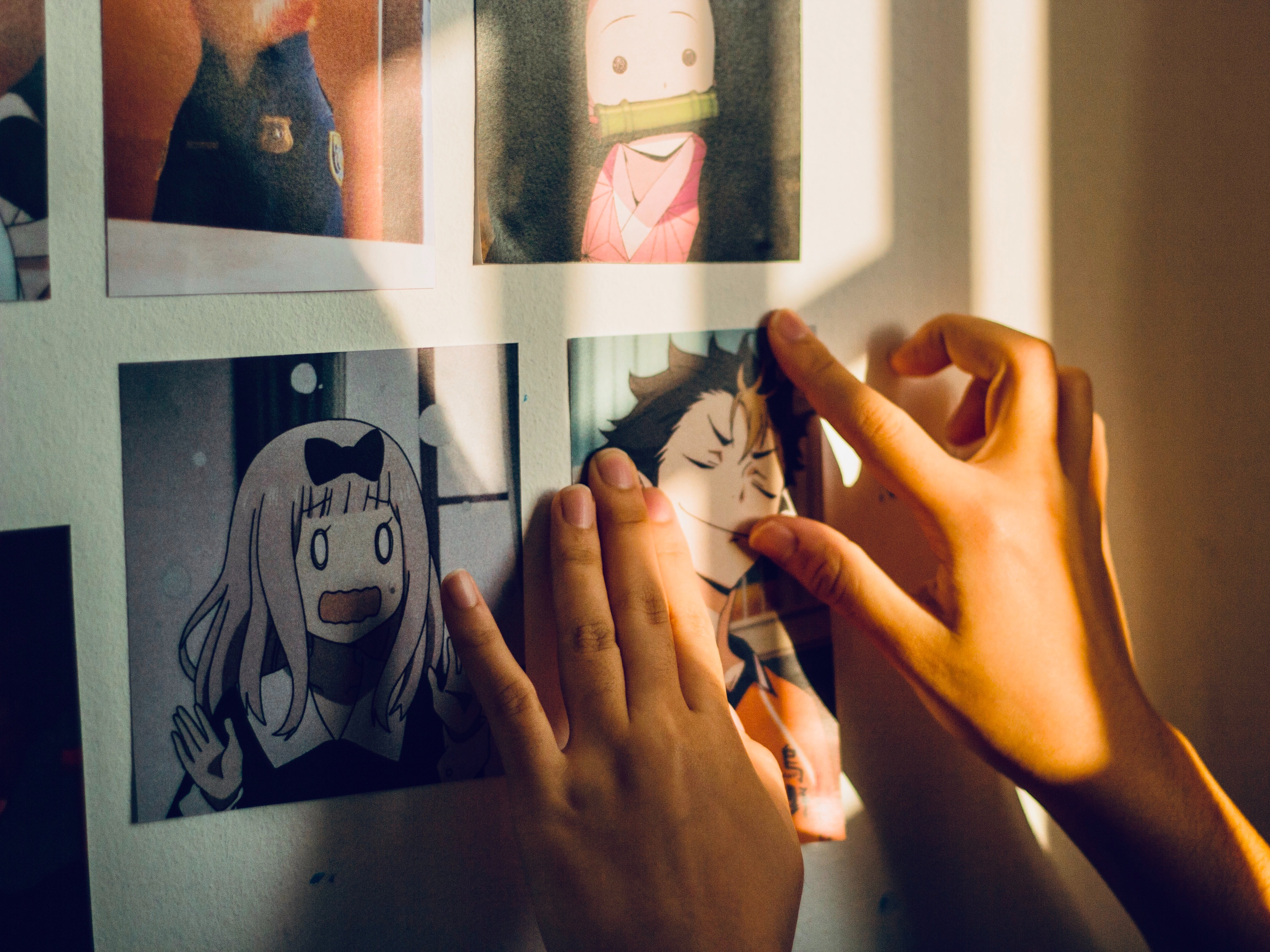 Photo of an anime fan hanging printed out pictures of anime characters on their wall. Photo courtesy of Gracia Dharma on Unsplash.