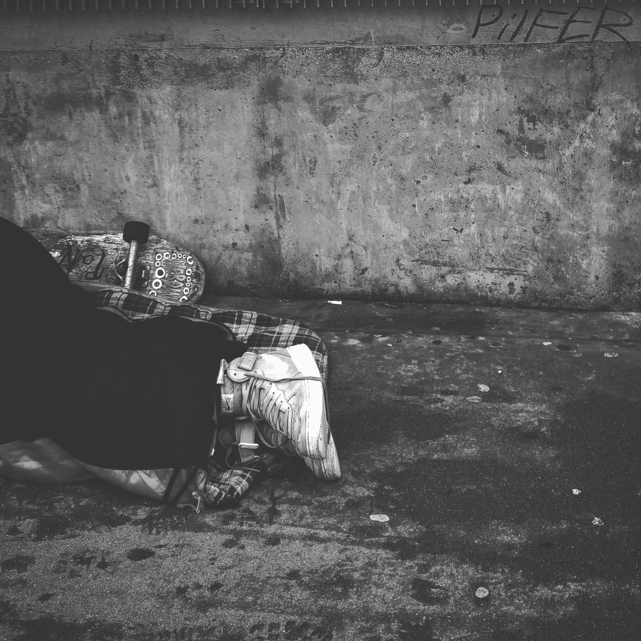 A person wearing white high-top sneakers laying on the ground. Photo courtesy of Taufiq Klinkenborg on Pexels.