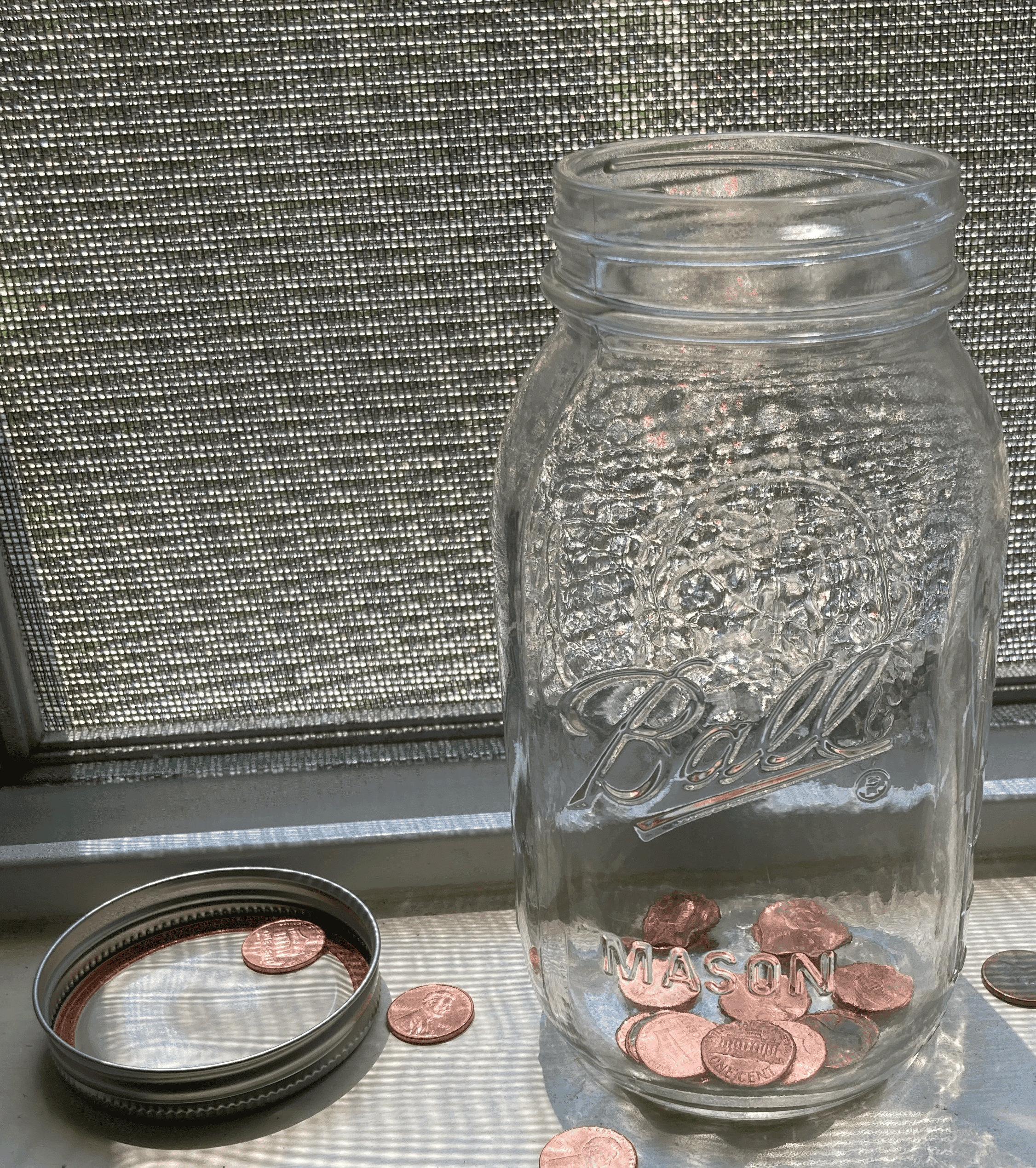 An open mason jar with a few pennies inside and surrounding it. Photo courtesy of the author.