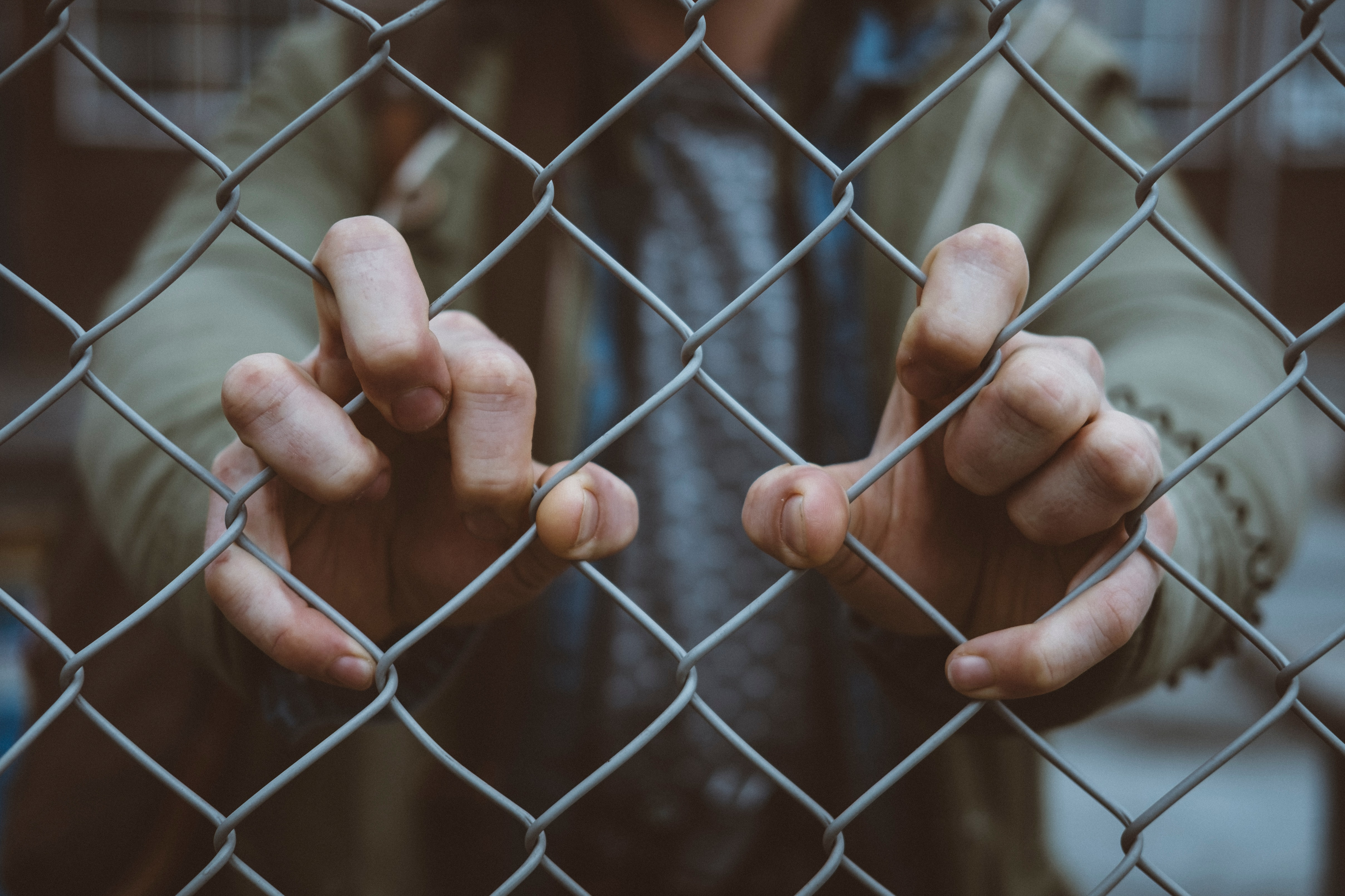 Person behind a cage holding on to it. Photo courtesy of Mitchel Lensink on Unsplash.
