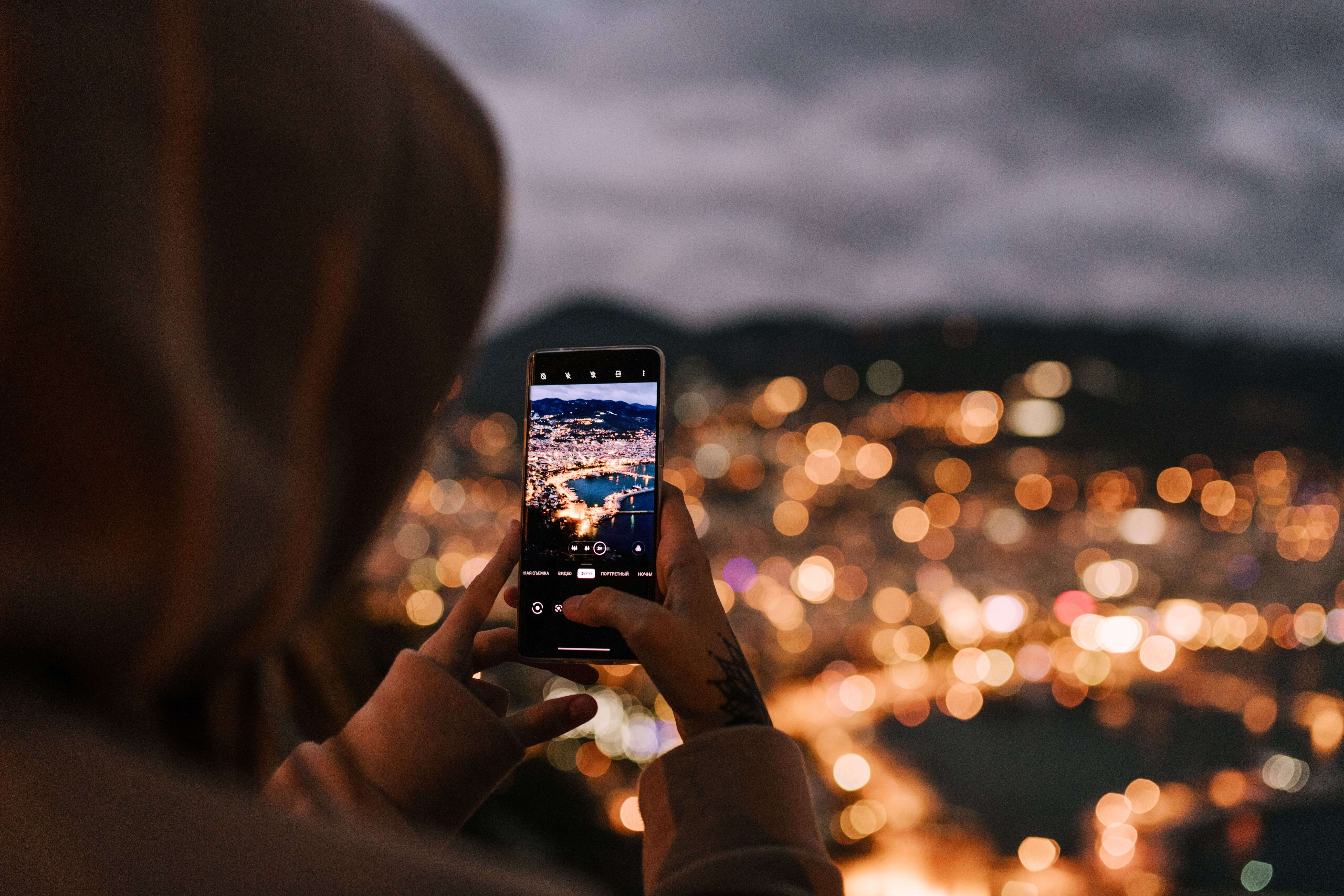 An over-the-shoulder view of someone taking a photo using their phone. Photo courtesy of Julia Volk on Pexels.