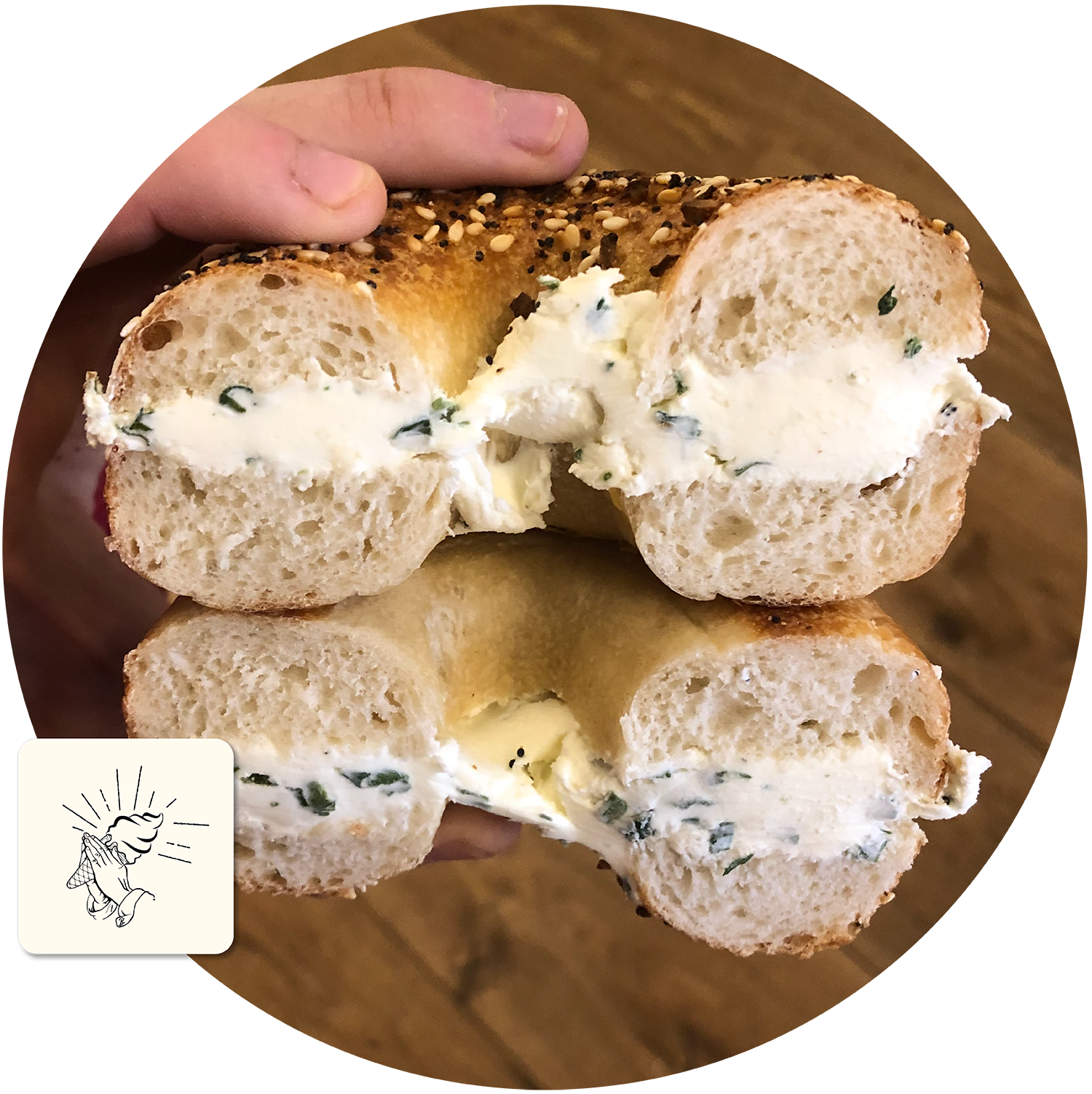 A man's hand holds a bagel cut in two with cream cheese in the middle.