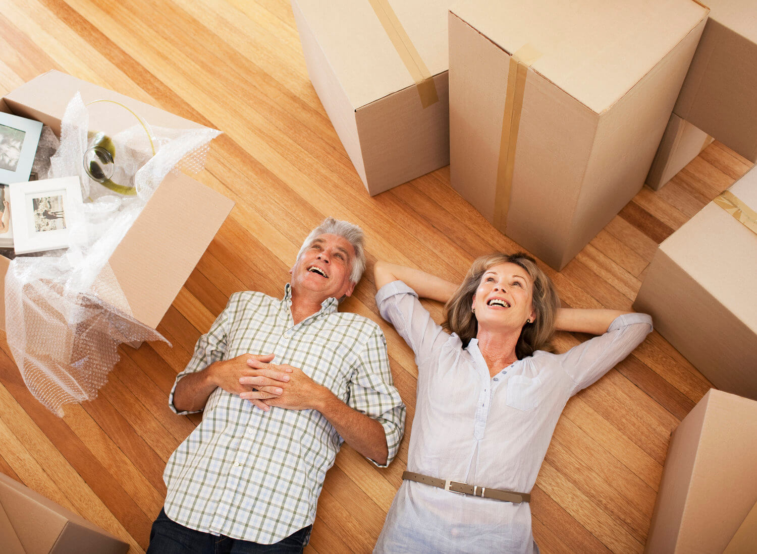 Real estate investors laying on floor smiling after buying a property