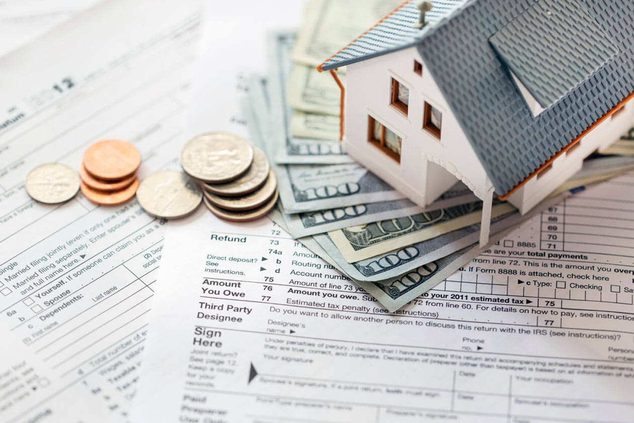 House and money next to a mortgage agreement