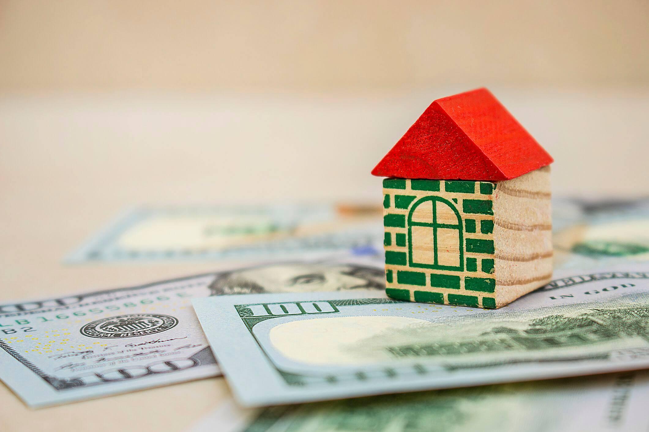 Mini house on top of 100 dollar bills