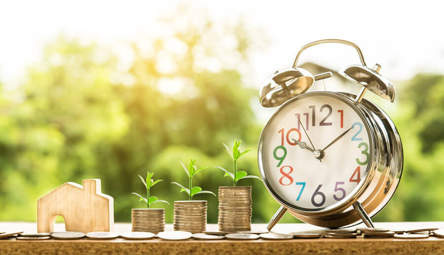 Buy and hold investing with a wooden house, quarters, and a clock