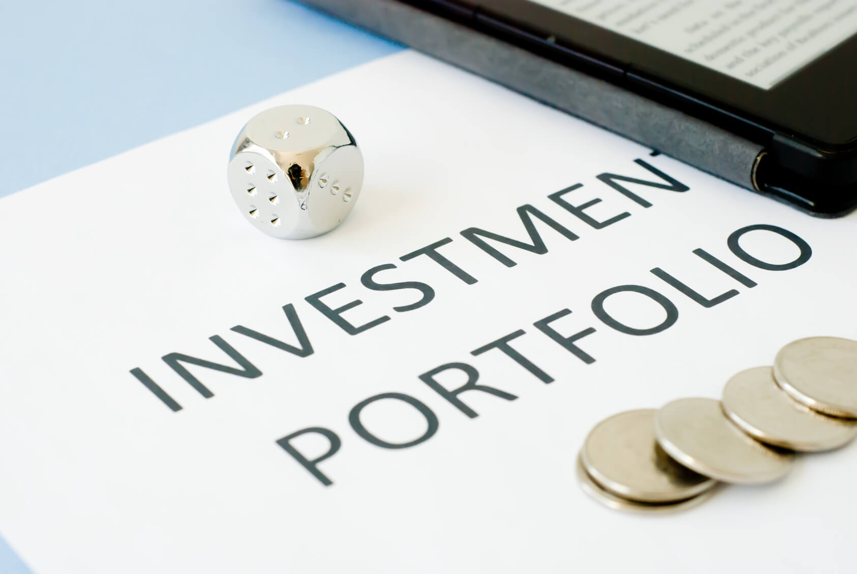 Investment portfolio on a desk, with coins and a dice