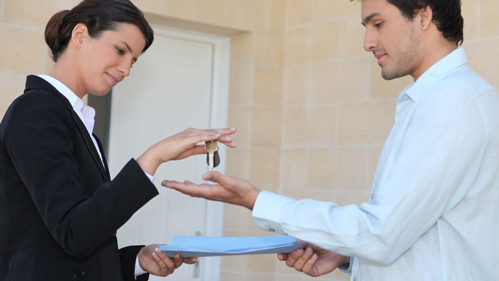 Woman (landlord) handing keys to a man (tenant)