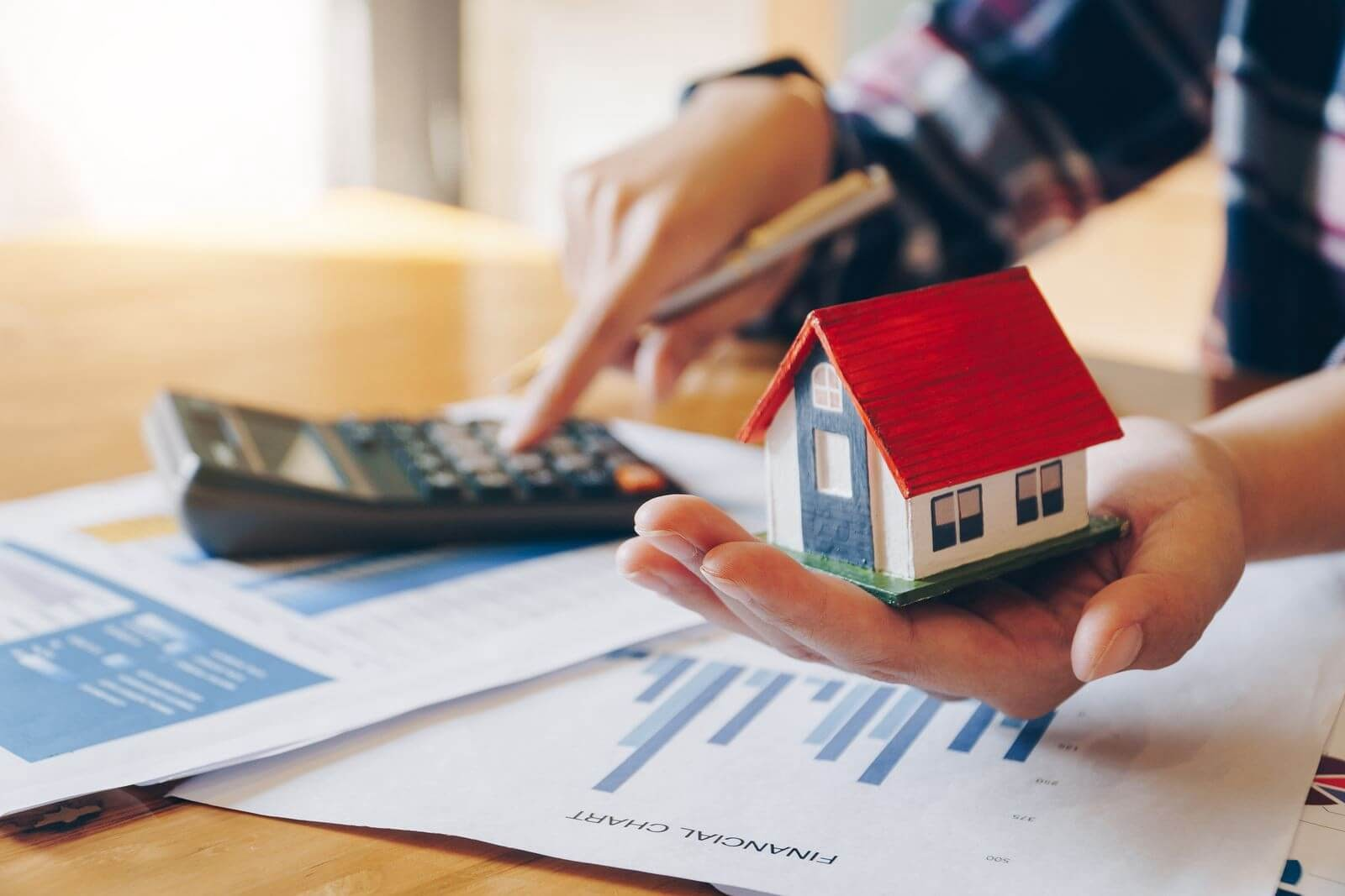 Person using calculator and holding a mini-house in the other hand with real estate documents on the side