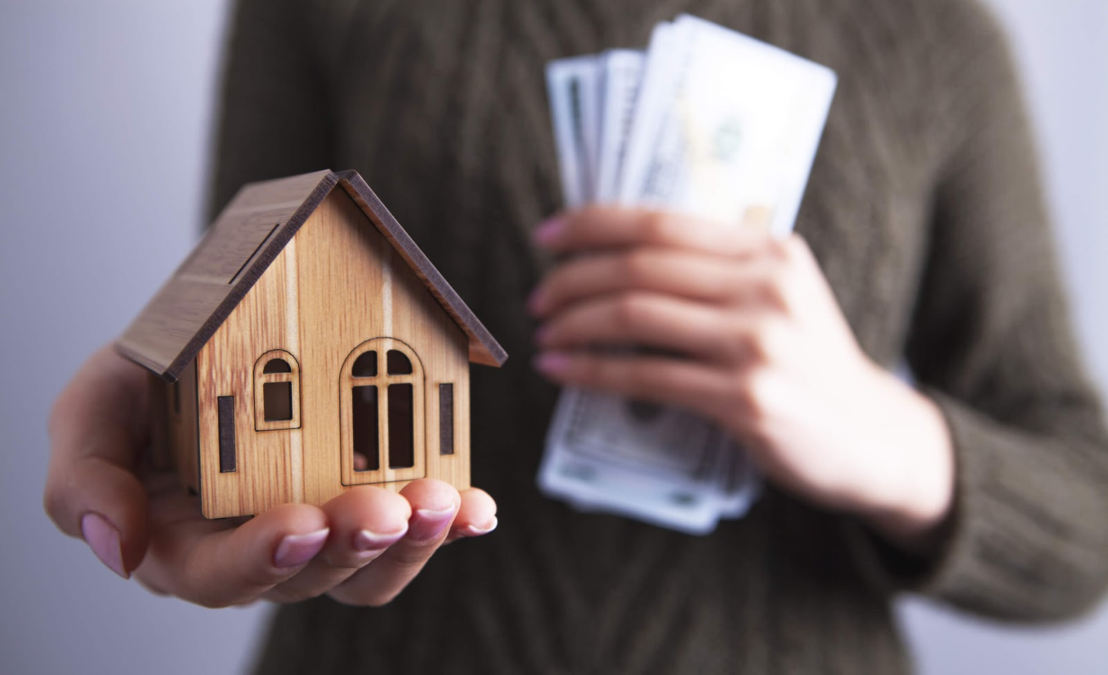 Person holding cash in one hand and holding out a mini-house in the other hand