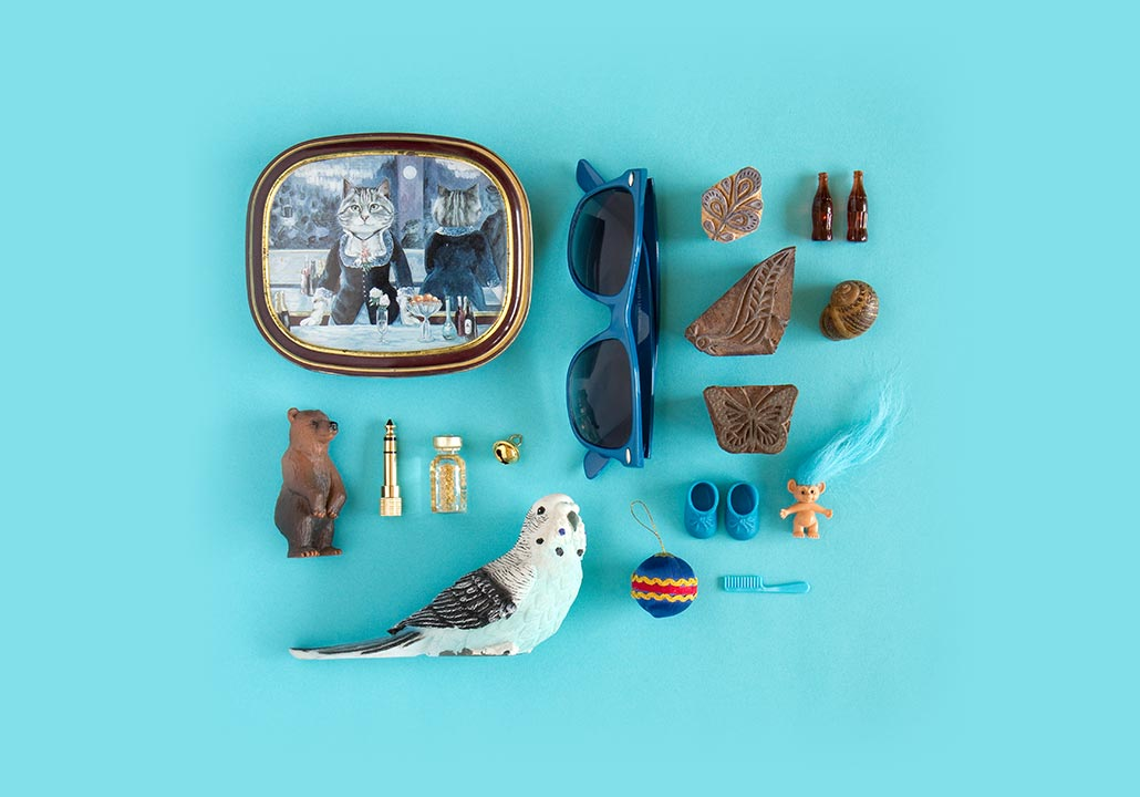 Thumbnail image for the Memorabilia project, representing a top view of a collection of various little blue, golden and brown personal objects, like a bear figurine or a pair of blue sunglasses, on a light blue background.