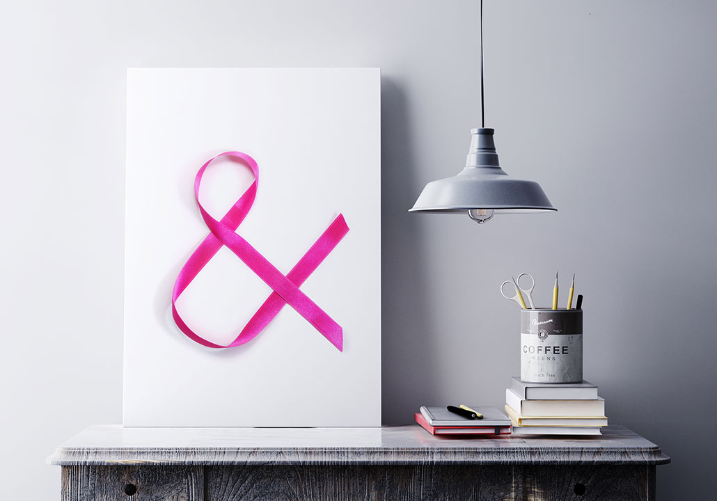 Thumbnail image for the Pink Link project, representing a framed poster of a large ampersand made of pink ribbon, laid on the left side of a console, along a light grey wall, with an industrial style ceiling light hanging on the right.