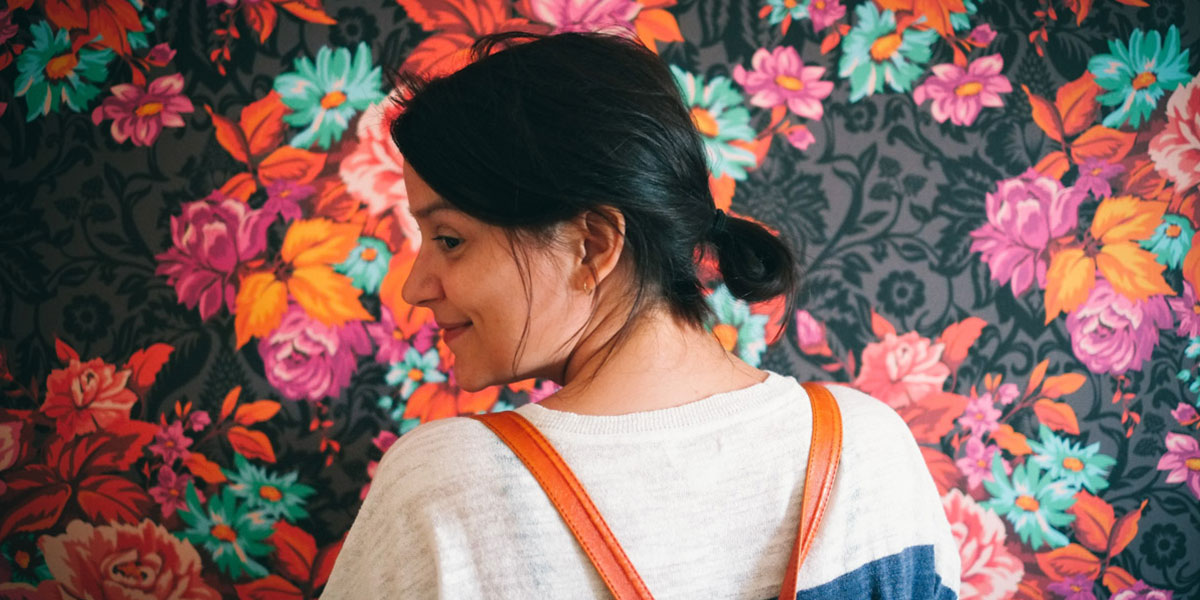 Cropped picture of Marie's profile view and upper back, smiling and wearing  a white shirt, in front of a floral wallpaper with large pink, orange and turquoise flowers on a dark background.