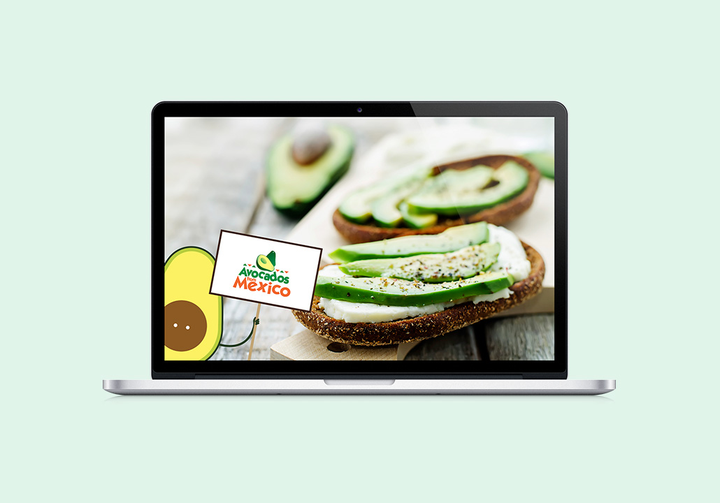 Thumbnail image for the Avocados from Mexico project, representing a laptop computer display with a picture of two avocado toasts and half of an avocado, with the Avocados from Mexico illustrated character, Avoman, in the foreground, holding a sign with the Avocados from Mexico logo.