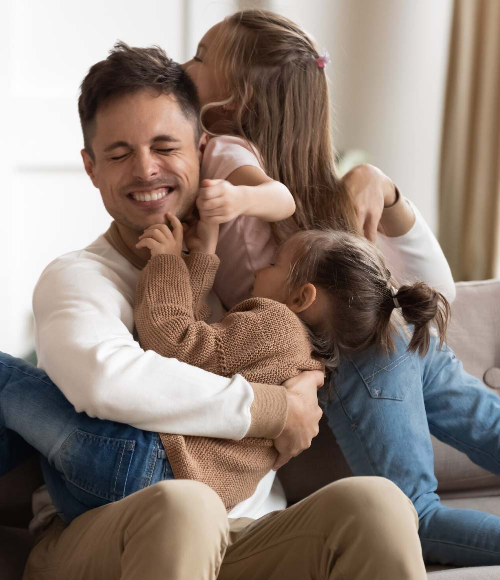 Smiling man hugs his two young daughters.