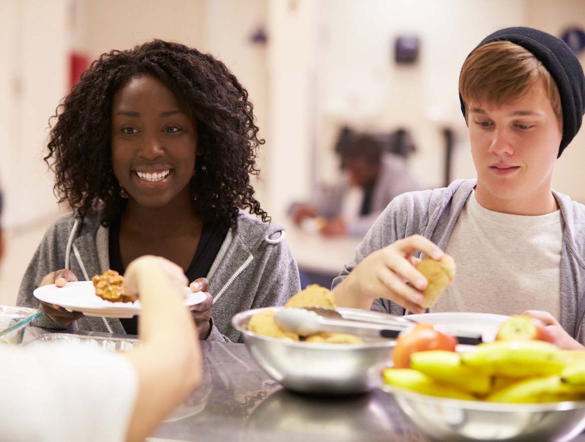 Two teenagers happily eating a meal.