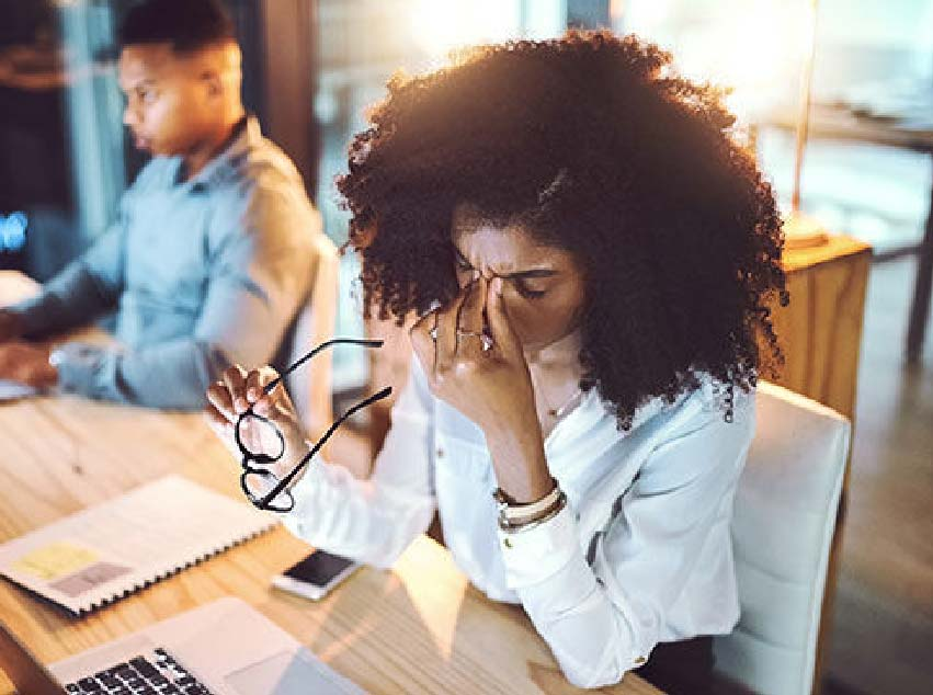 Woman sitting depressed with face in her hands at office.