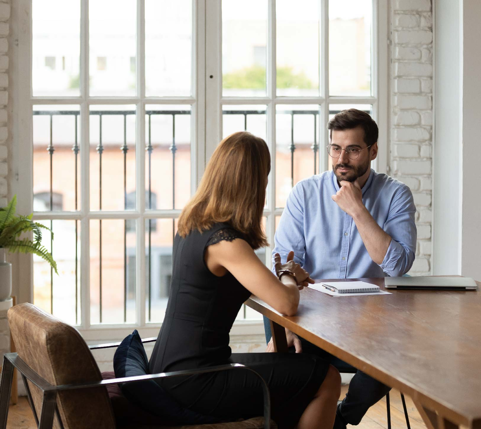 Boss talking with employee in office setting at a table.