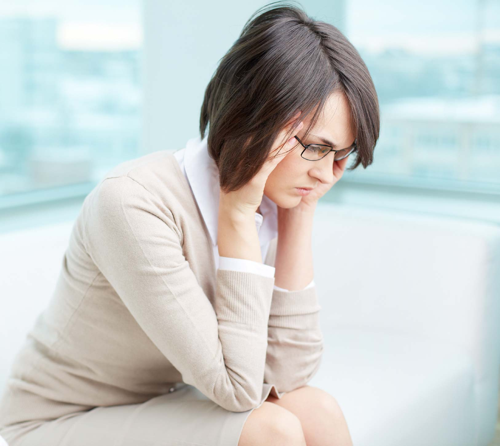 Woman sitting depressed with face in her hands at home.
