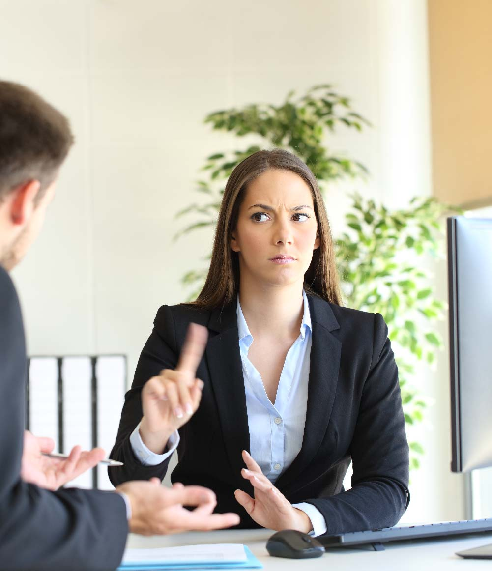 Woman refusing advances from her boss in office setting.