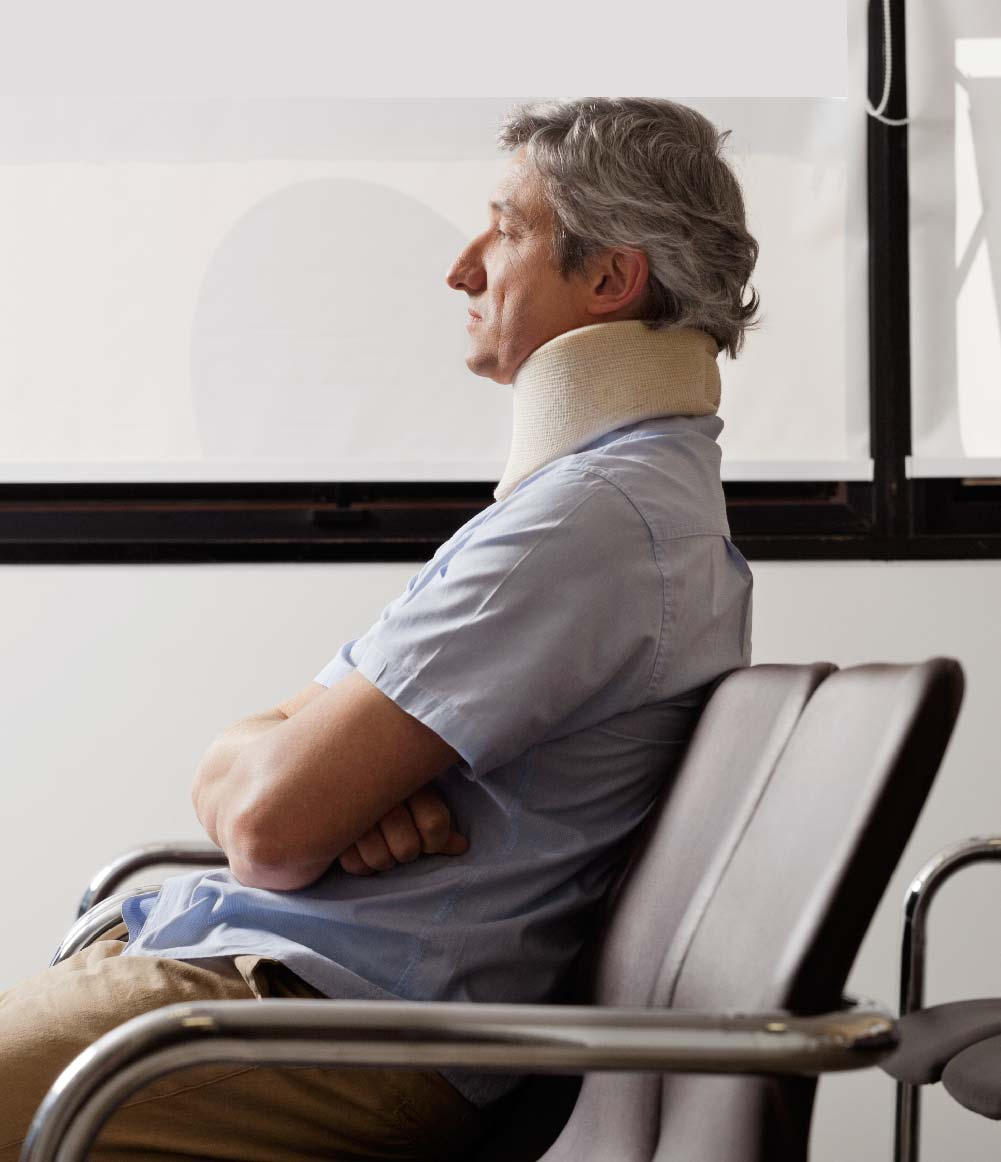 Injured man with neck cast sitting on chair, concerned.