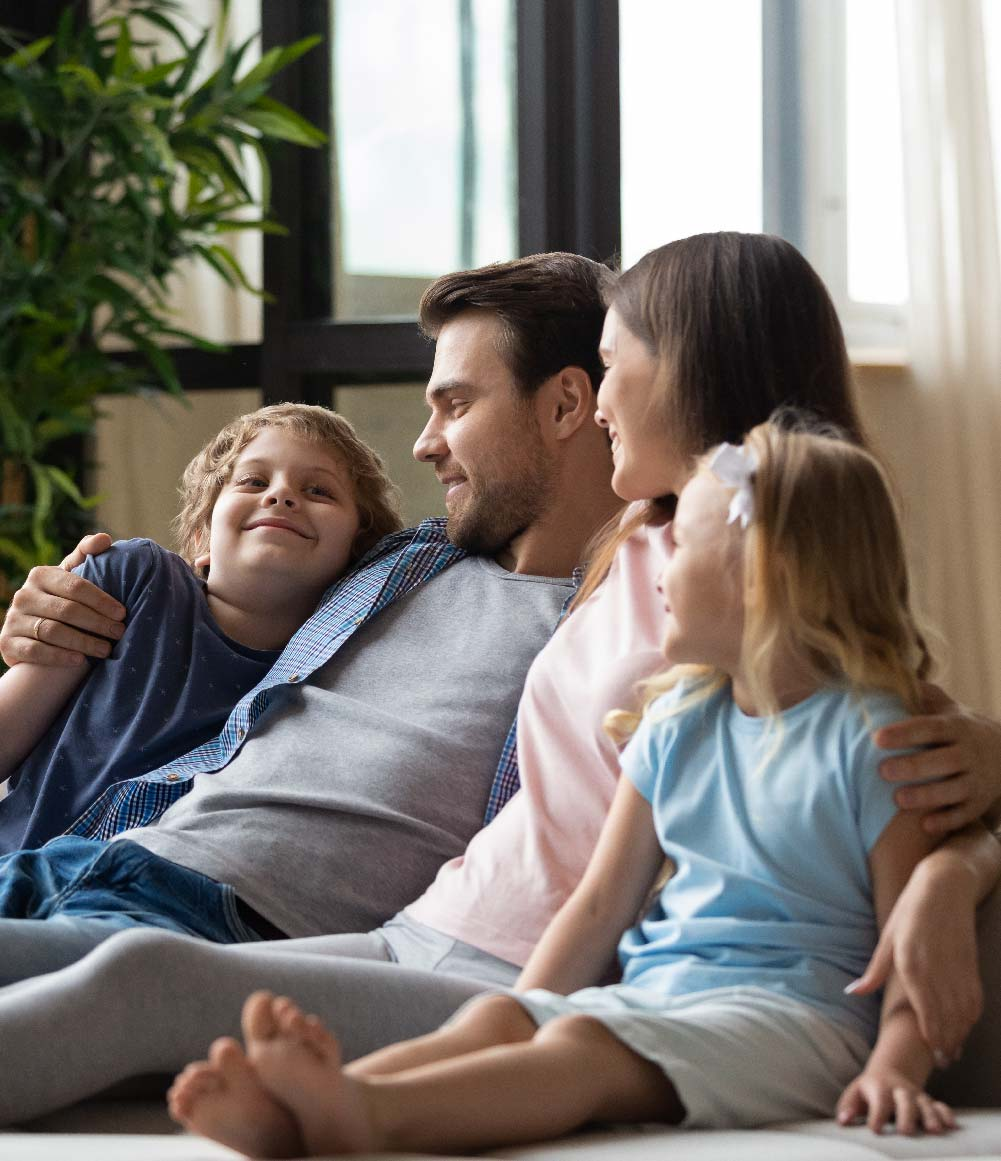 Man sitting on sofa smiling with his wife and two young children.