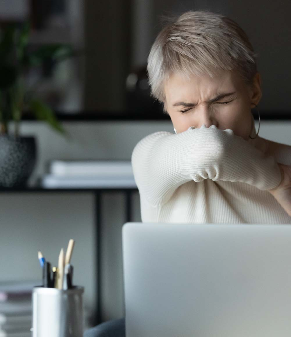 Woman covering mouth, coughing at while working on her lap top computer.