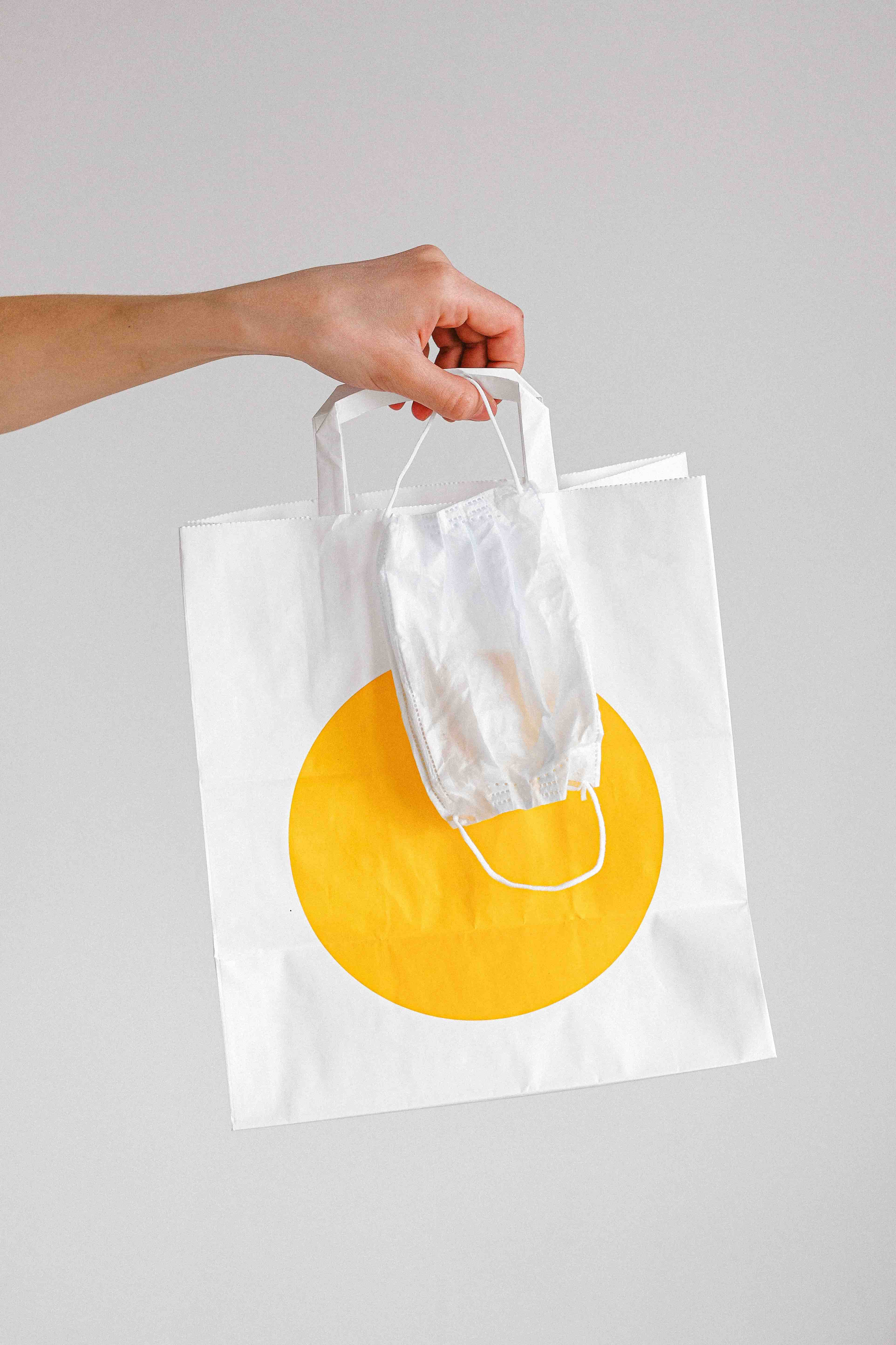 A hand holding a clothing shopping bag and face mask
