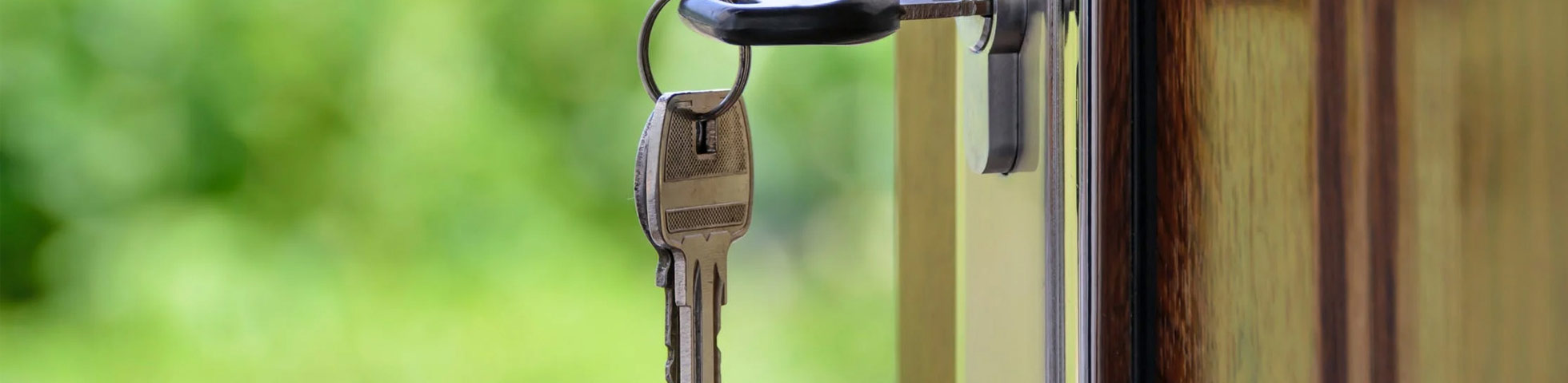 Photography of keys on a door.