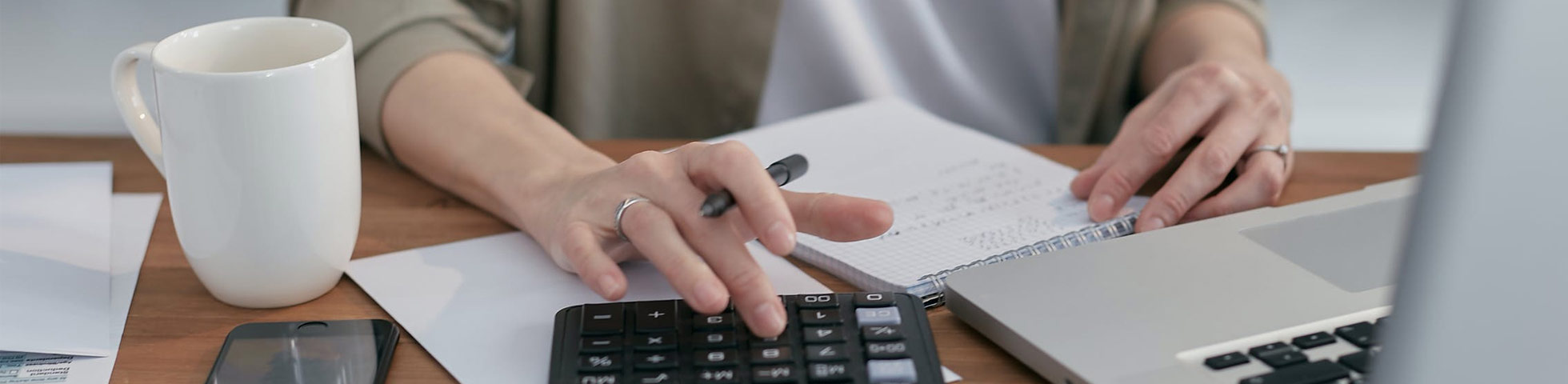Woman working on a computer, using a calculator.