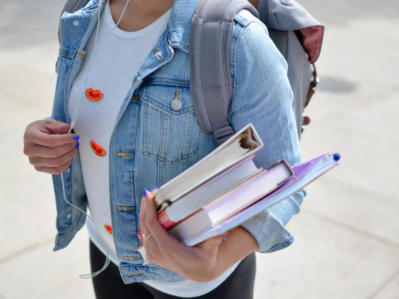 A girl carrying books.