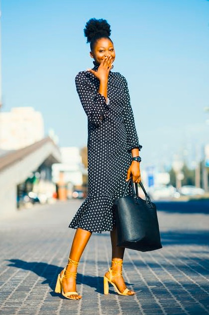 Black Woman modeling a polka-dot dress on the street.