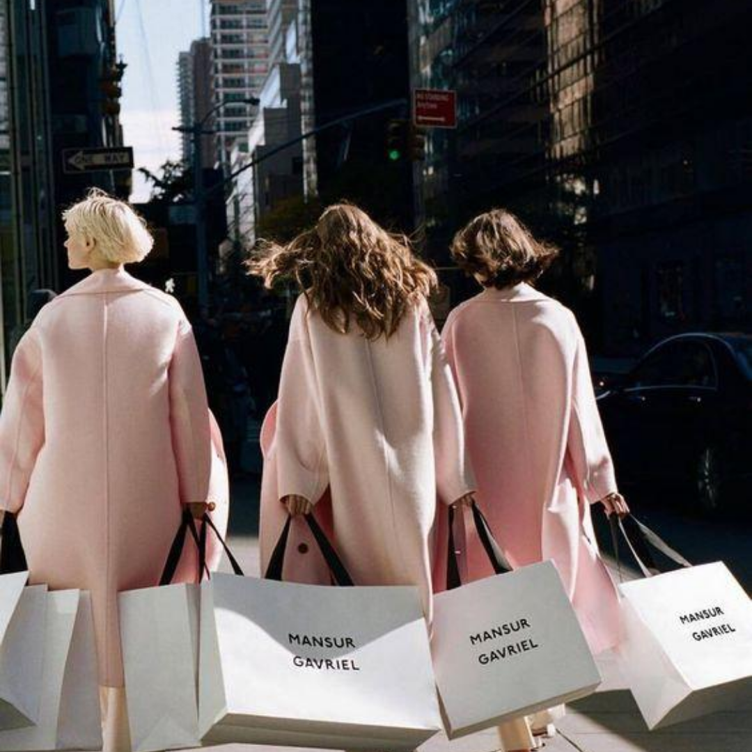 Three women dressed in pink carrying shopping bags in the city
